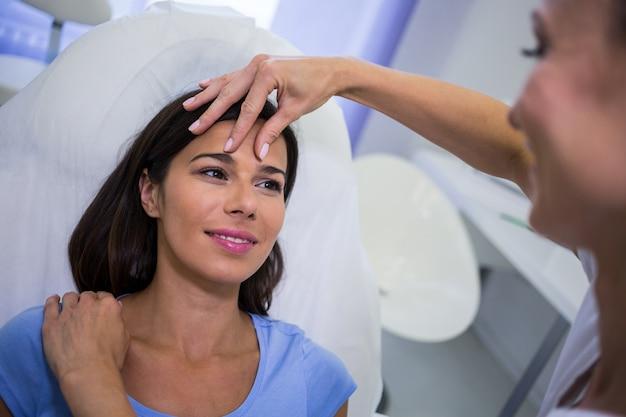 Врач осматривает лицо пациентки в клинике