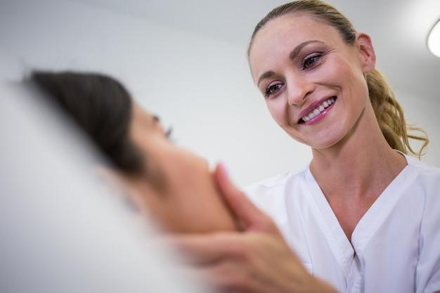 클리닉에서 여성 환자 얼굴을 검사하는 의사