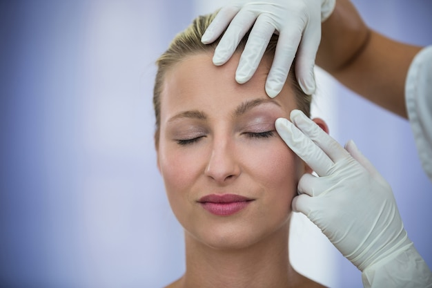 Doctor examining female patients face from cosmetic treatment