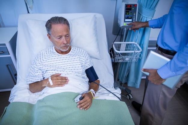 患者の心拍数を調べる医師