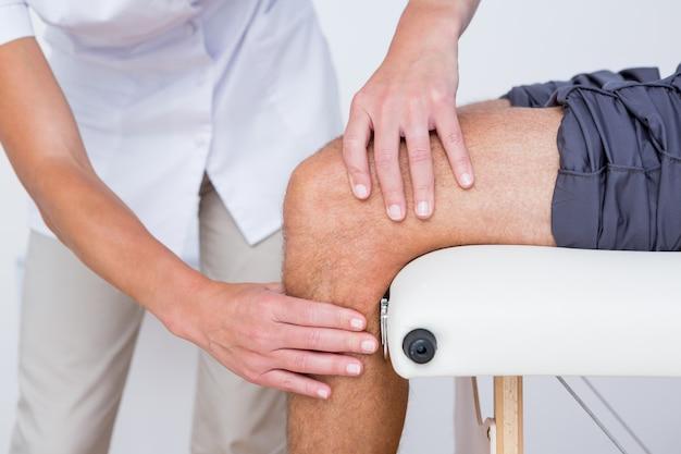 Doctor examining her patient knee