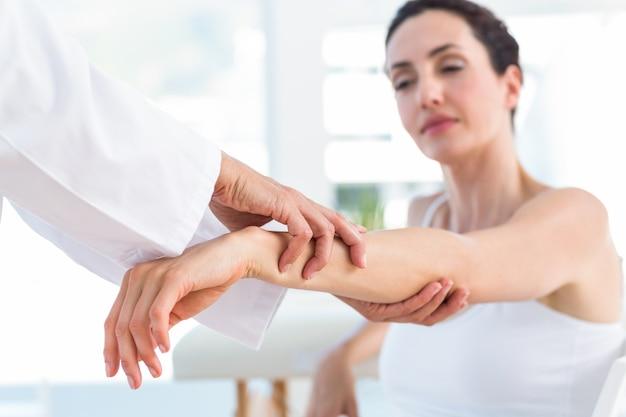 그녀의 환자 팔꿈치를 검사하는 의사