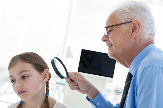 Доктор осматривает больное ухо с помощью увеличительного стекла