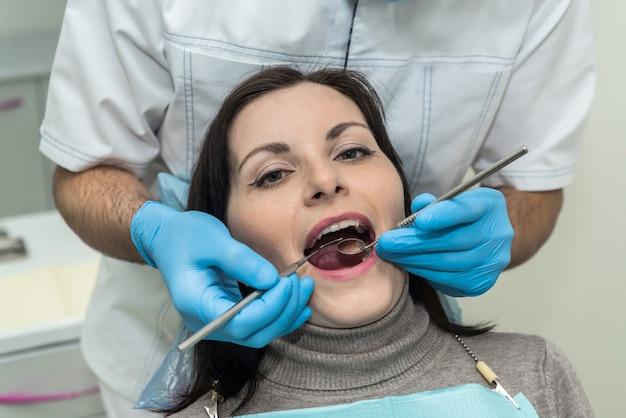 치과에서 도구로 환자의 치아를 검사하는 의사