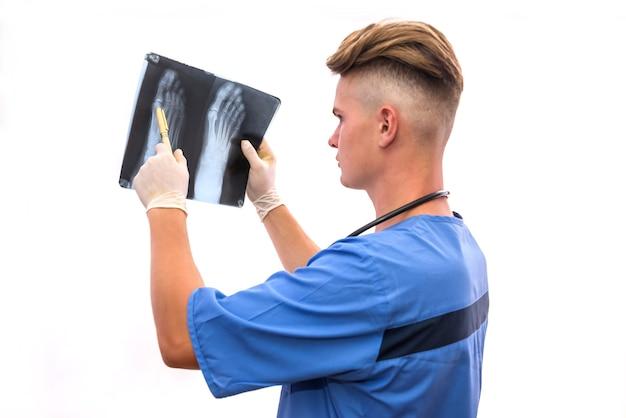 医師が患者のx線検査を行います。足のレントゲン写真を保持し、それを見ている青い制服を着た若い男
