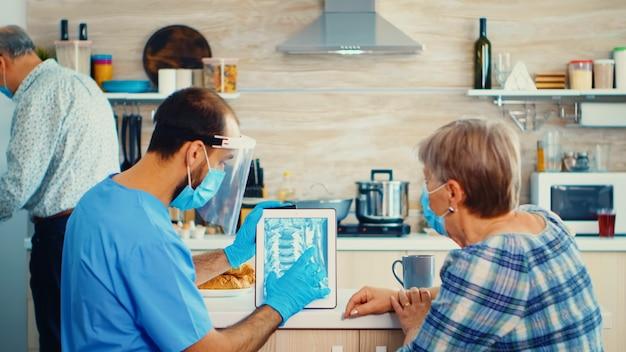 의사는 얼굴 마스크를 착용하고 가정 방문 중에 태블릿 pc에서 환자 엑스레이를 검사합니다. 남성 간호사가 질병 예방에 대해 논의하고 은퇴한 노인 여성을 검사하는 노인 의료 방사선 사진.