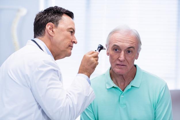 Врач осматривает пациентов уха с отоскопом