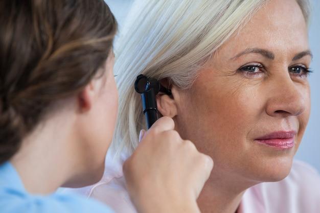 耳鏡で患者の耳を調べる医師