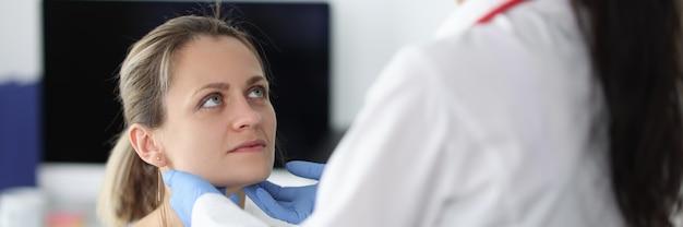 Врач осматривает поднижнечелюстные лимфатические узлы пациентов в клинике