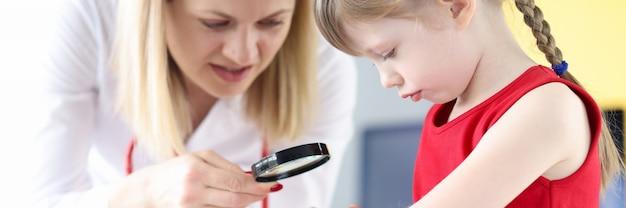 虫眼鏡で小さな女の子の手に色素性母斑を調べる医師。子供の概念における皮膚病の治療