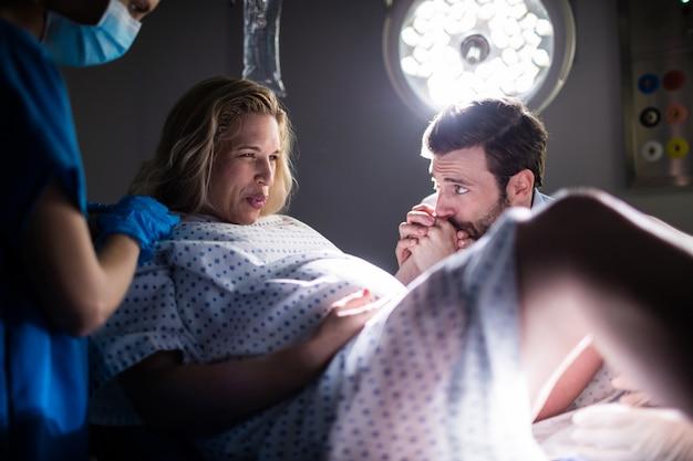 男が手術室で彼女の手を握りながら配達中に妊娠中の女性を調べる医師