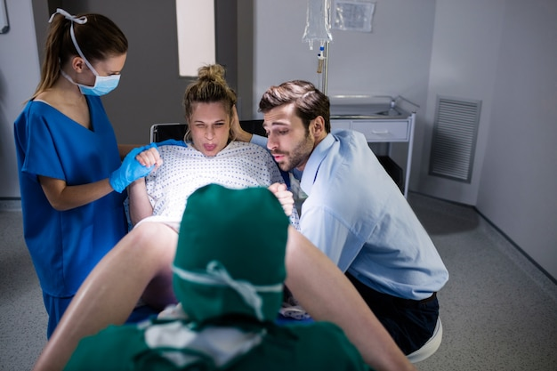 Doctor examining pregnant woman during delivery while man holding her hand in operating room