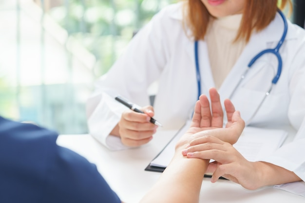 Doctor examining pulse of patient by hands, medical diagnosis concept