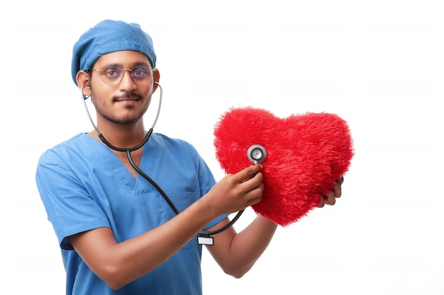Doctor examining a red heart shaped pillow with a stethoscope against white background.