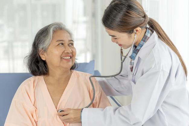 病院のベッドの患者-医療とヘルスケアのシニアコンセプトでシニア高齢女性患者を調べる医師