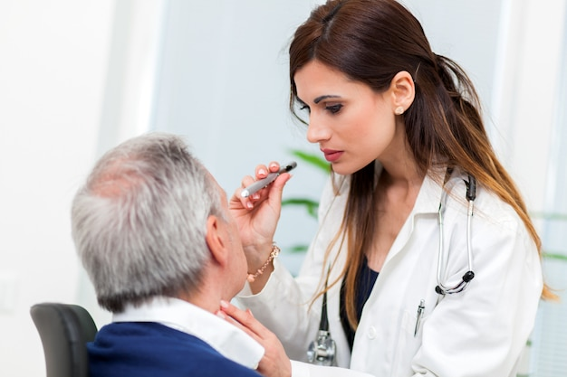 Doctor examining senior male patient's eyes