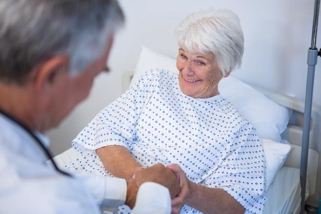 Врач осматривает старшего пациента в палате