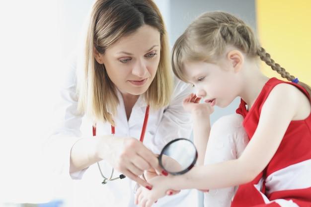 Врач изучает кожу на руке маленькой девочки с помощью увеличительного стекла в клинике