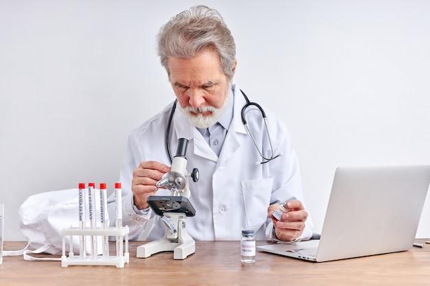 의사가 검사하고 사무실의 튜브에서 코로나 바이러스 테스트를 연구하고 분석합니다. 프리미엄 사진