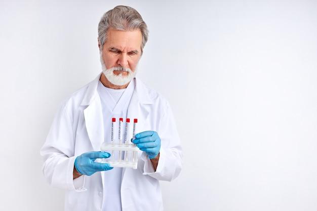 Врач осматривает, изучает тесты на коронавирус в пробирке, делает анализ