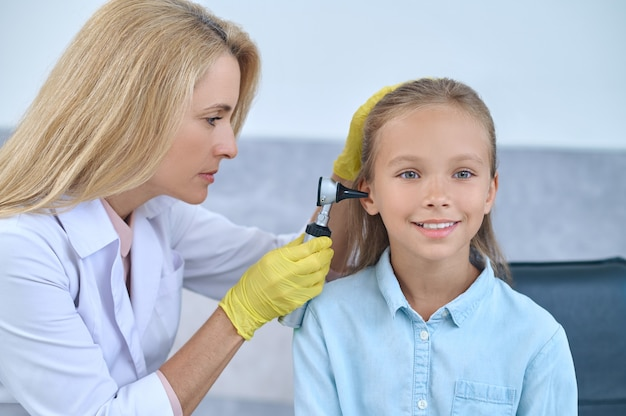 Врач осматривает ухо молодой девушки с помощью медицинского устройства