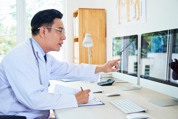X- 선 이미지를 검사하는 의사