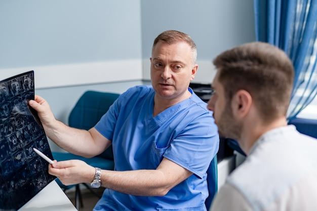 患者のx線検査を行う医師。テーブルに座っている男性の放射線科医。診療所の背景。