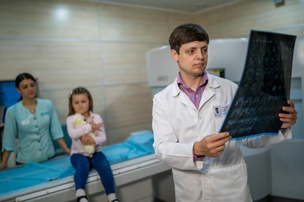 磁気共鳴画像装置の近くでx線画像を説明する医師。