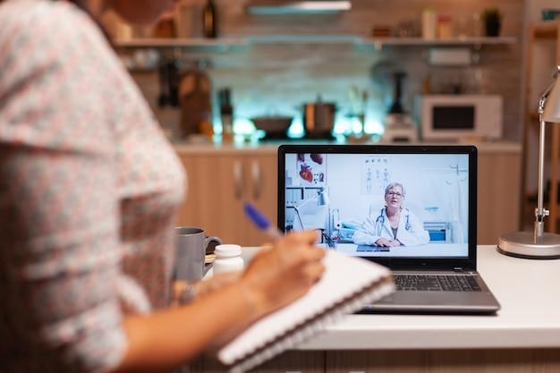 Врач объясняет диагноз во время видеоконференции с пациентом в полночь. врач консультирует больного из больничного кабинета во время виртуального осмотра, экрана, лекарства, назначает