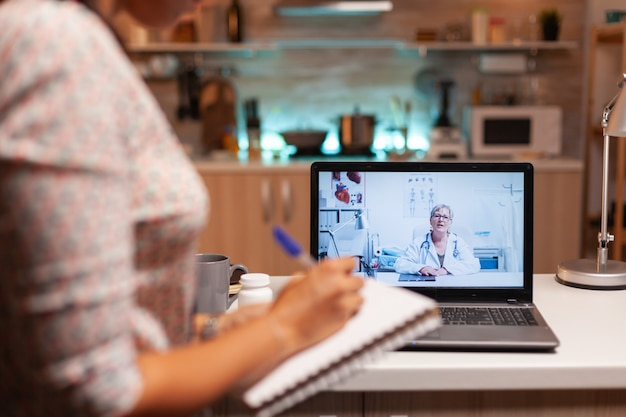 Doctor explaining diagnosis during a video conference with patient at midnight. physician giving consultation to sick patient from hospital office during virtual examination, screen, medicine, appoint