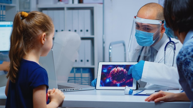 タブレットを使用して保護マスクを着用したウイルスの進化を説明する医師。コロナウイルス中のヘルスケアサービス、相談、治療を提供するバイザーと手袋を持った小児科医の専門家。