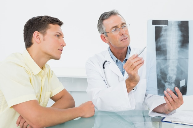 Doctor explaining spine xray to patient in office
