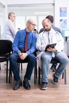 Доктор объясняет результаты теста старшему мужчине в зоне ожидания больницы