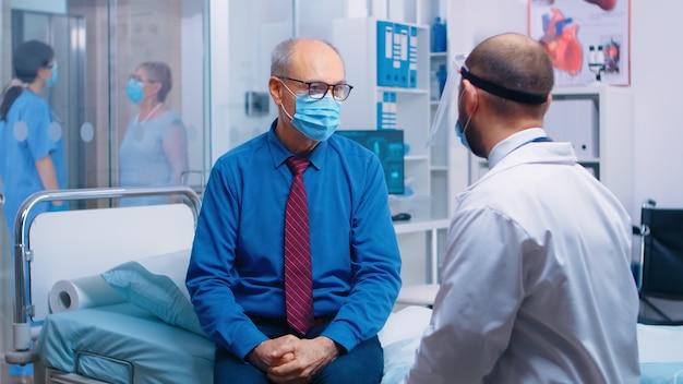 Covid-19 동안 따라야 할 단계를 환자에게 설명하는 의사. 현대 사립 병원 또는 진료소. covid-19 전염병 동안 의료 의사 상담