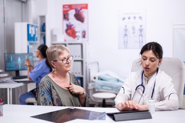タブレットを使用して患者に治療を説明し、クリニックで甲状腺の喉が健康に触れていることを確認する医師。病室に座って診察中に喉の痛みを医者に見せている年配の女性。
