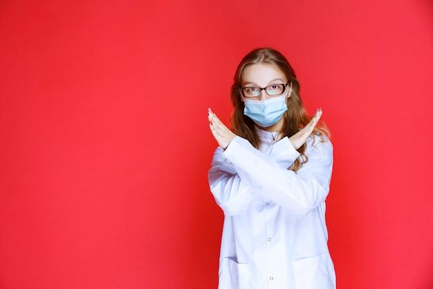 Dottore con una maschera facciale che si rifiuta di prendere il paziente.