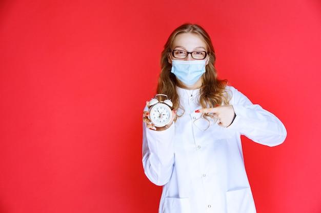 Dottore in maschera facciale che mostra un orologio che significa il tempo per l'assunzione di medicinali.