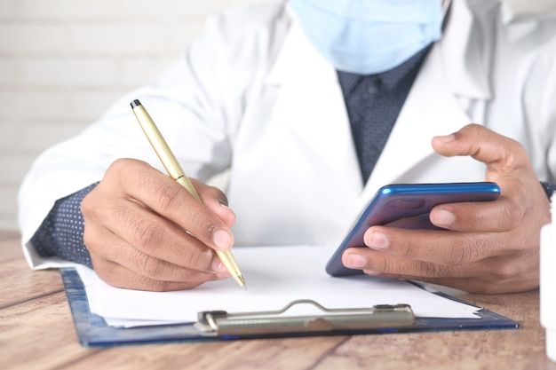 Doctor in face mask writing prescription and using smart phone