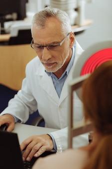 Доктор чувствует себя занятым. седовласый специалист по глазам чувствует себя занятым, глядя на ноутбук, наблюдая за зрением