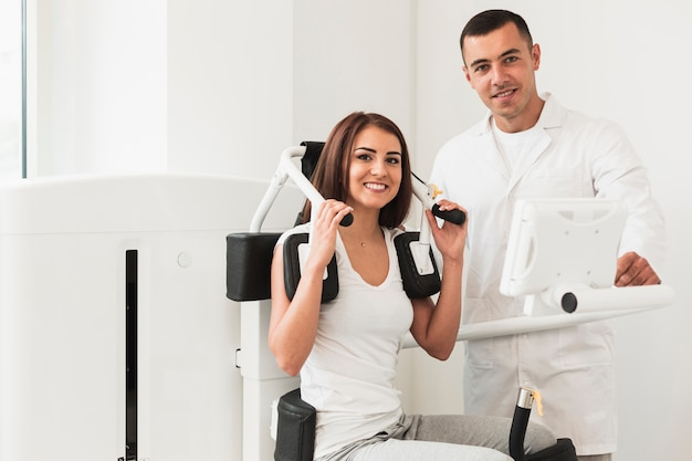 Doctor and female patient posing near medical machine