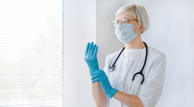 Doctor female preparing and wearing hand medical gloves. medic worker, healthcare protection.