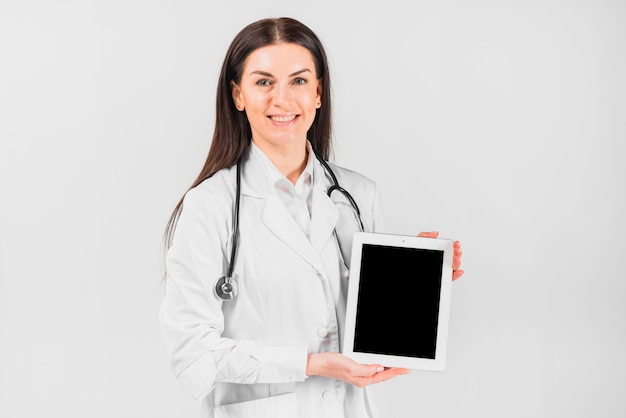 Doctor female smiling and showing tablet
