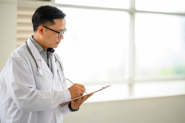 Doctor filling document on clipboard