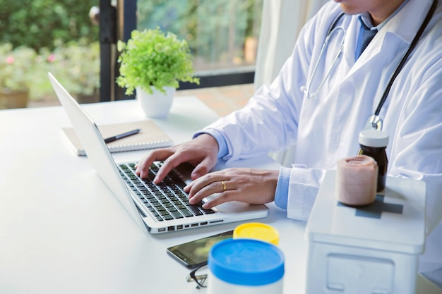 医師がラップトップで患者の情報を入力する