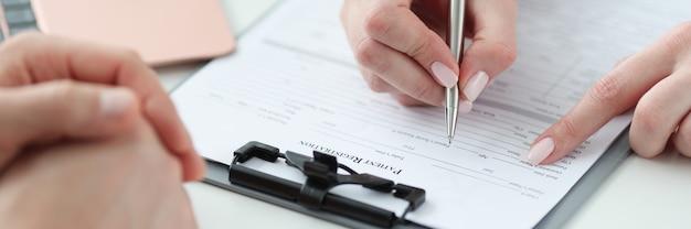 クリニックのクローズアップで患者の病歴を記入する医師