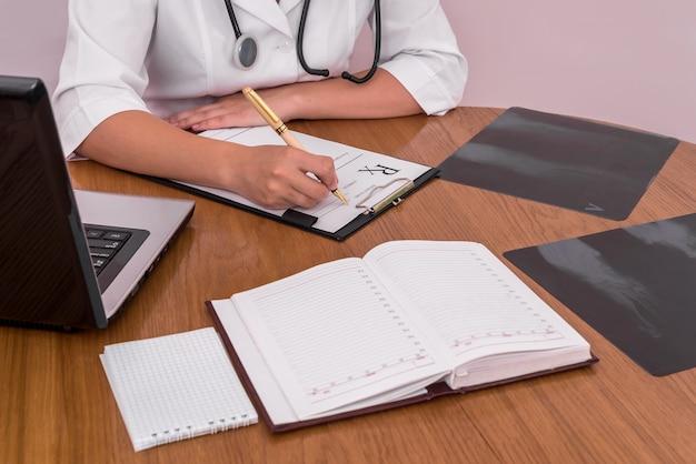 木製のテーブルに患者のx線で処方箋を記入する医師