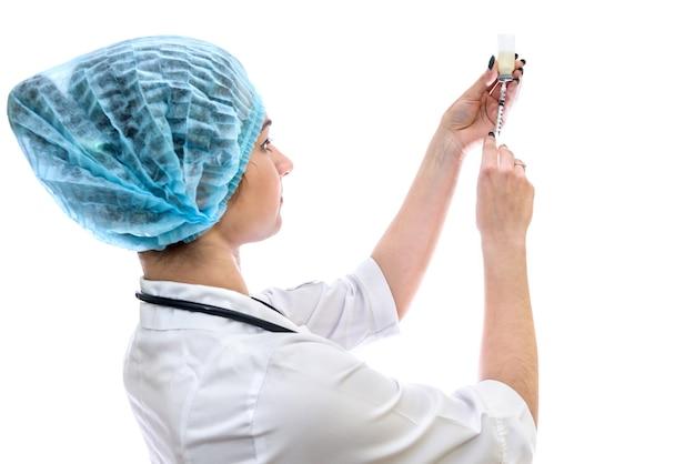 白で隔離されたアンプルからの薬で注射器を充填する医師