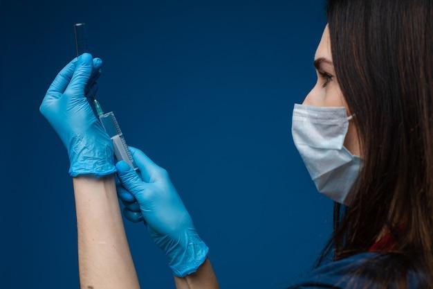 Доктор заполнения шприца с вакциной. covid-19. заполнение шприца вакциной или лекарством из ампулы.