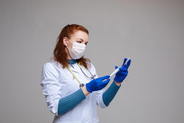 ワクチンで医師充填シリンジ。赤い髪の専門の医者