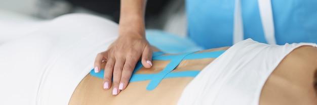 医師は腰痛のある患者の脊椎にキネシオテープを固定します
